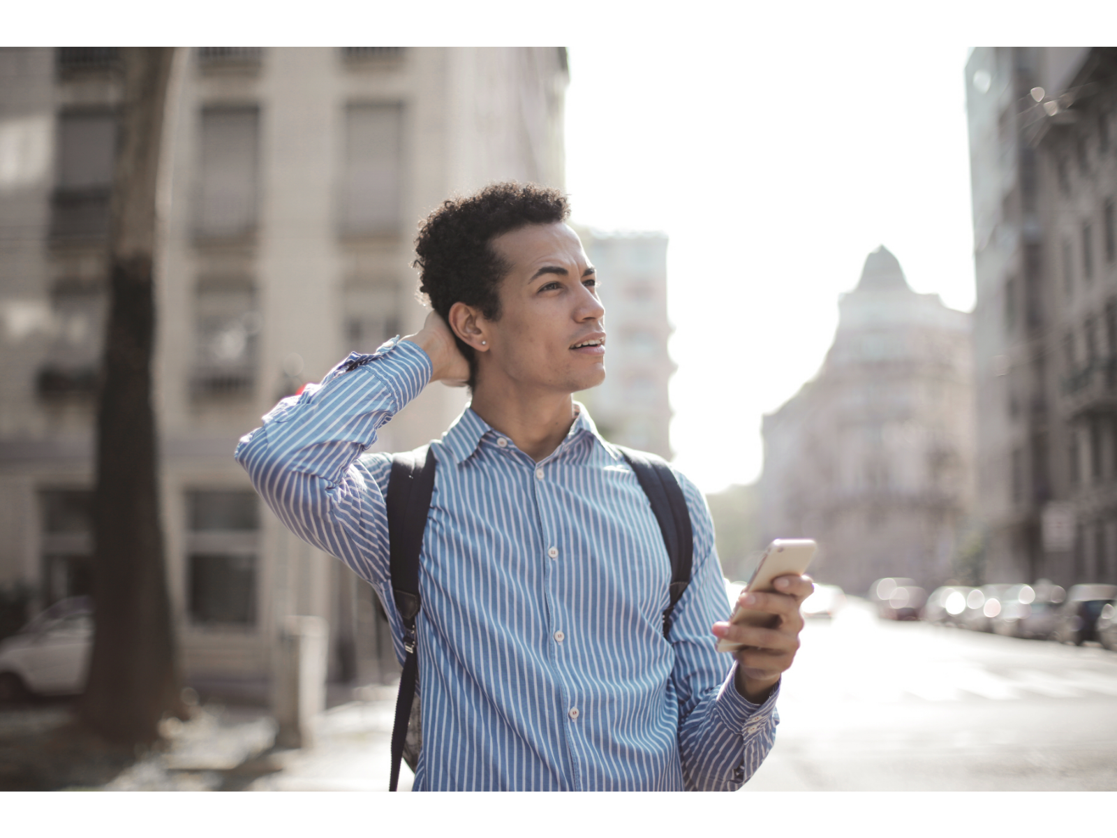 Mildly confused man stands on a city sidewalk and looks off in the distance while holding a smartphone.